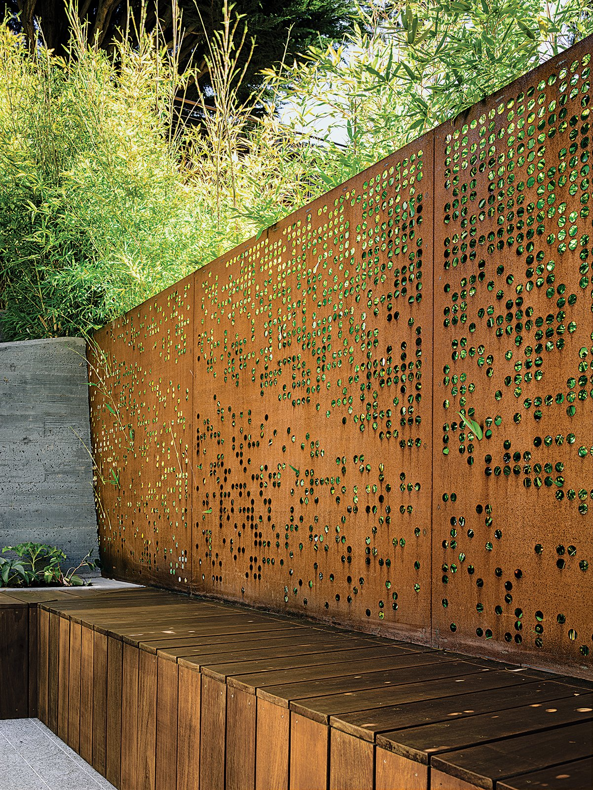 Outdoor and Metal Fences, Wall With input from her clients, Barensfeld used a computer to generate the circular patterns that were carved into a pair of Cor-Ten steel screens with a water-jet cutter. The perforations allow light and the green of the surrounding Koi bamboo to filter into the space while preserving privacy.  garden