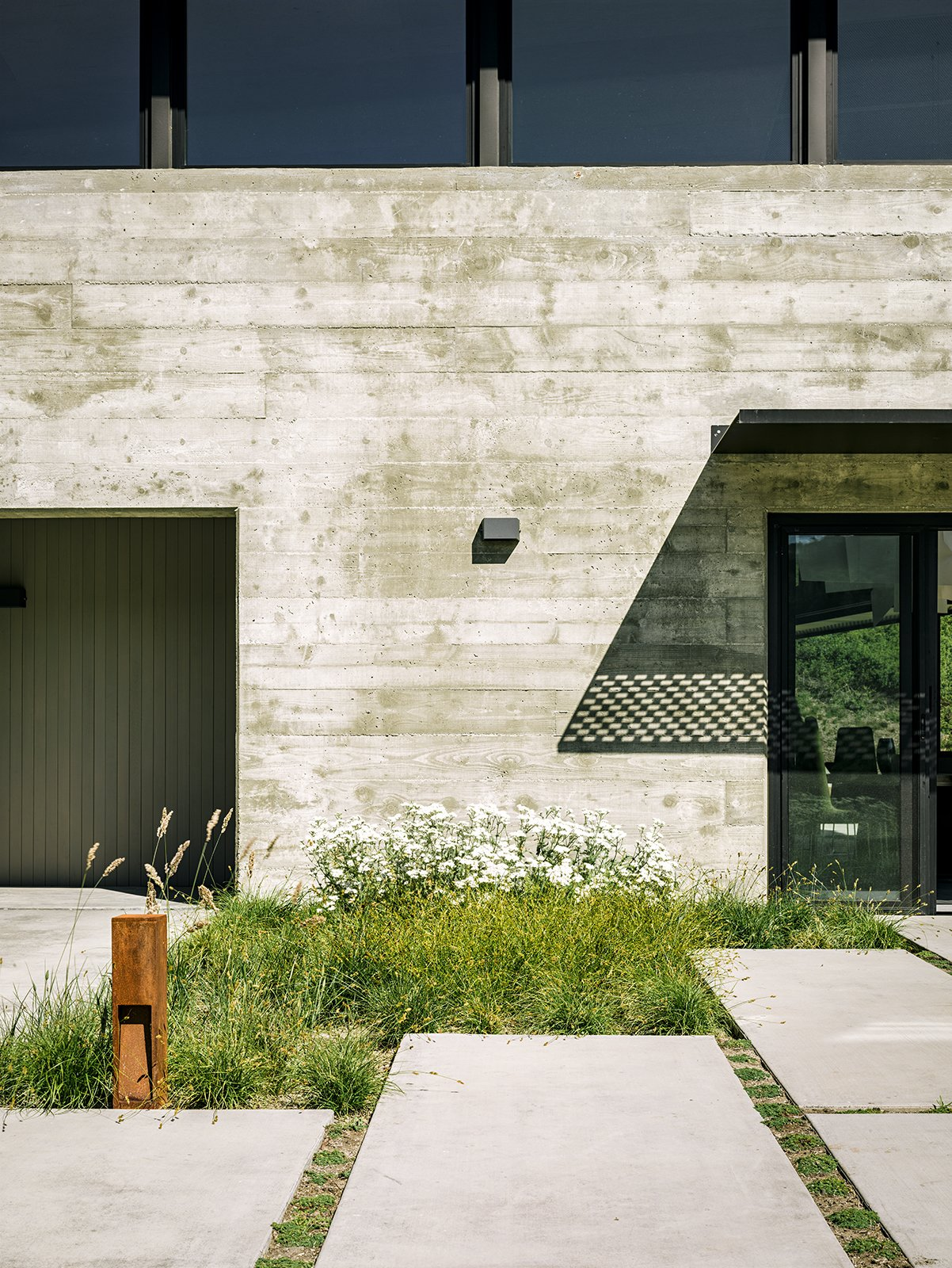 """Exterior, Butterfly RoofLine, House Building Type, Concrete Siding Material, Metal Roof Material, and Metal Siding Material More native grasses set the tone near the generously sized concrete pavers leading to the entrance. """"We didn't want the planting to feel like a country cottage garden—that would have felt disconnected with the view behind it,"""" Trainor says.  Photo 6 of 10 in Sustainable Retirement Home in Tune with California Landscape"""