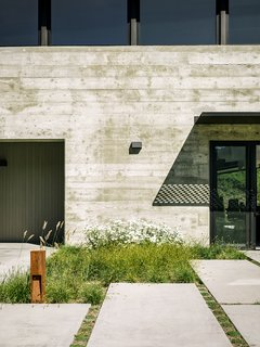 "More native grasses set the tone near the generously sized concrete pavers leading to the entrance. ""We didn't want the planting to feel like a country cottage garden—that would have felt disconnected with the view behind it,"" Trainor says."