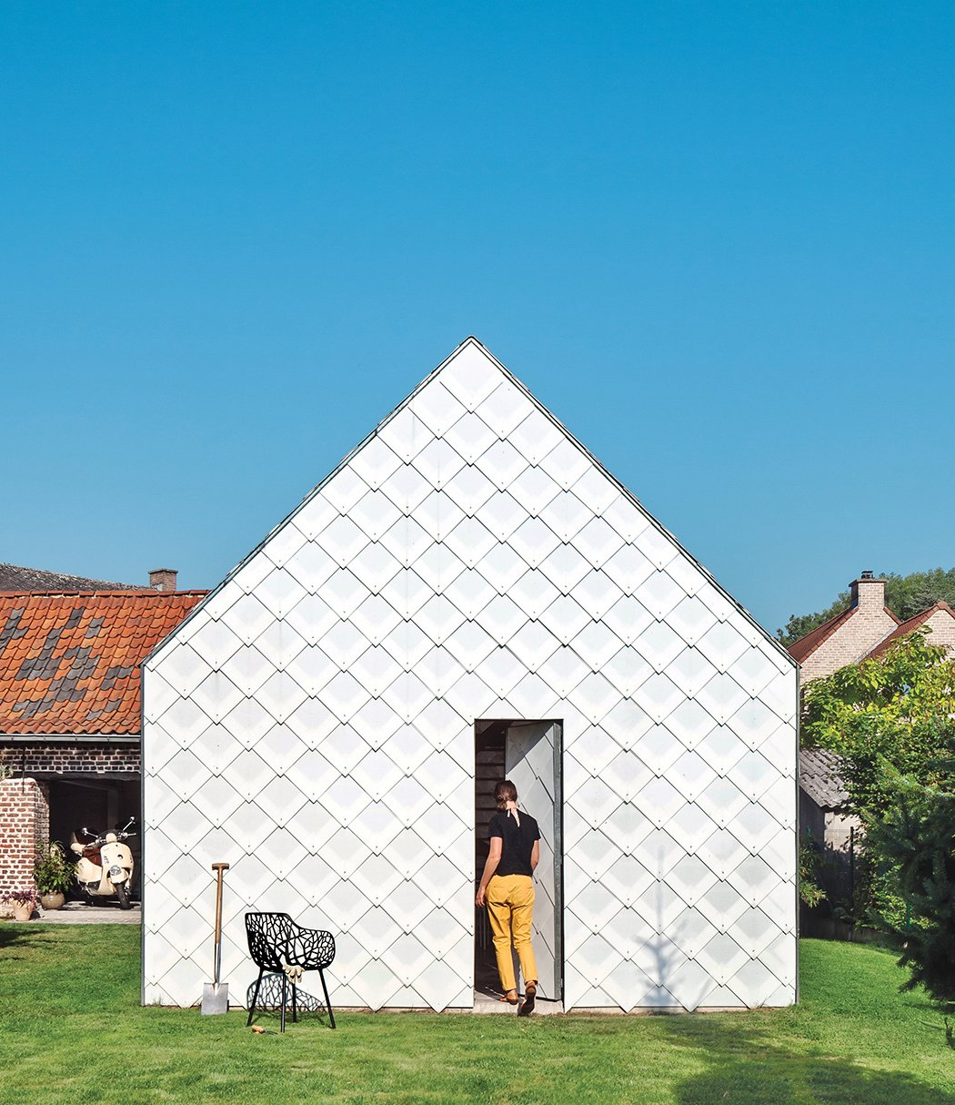 Grass, Trees, and Shed & Studio Architect Indra Janda hand-cut sheets of polycarbonate into 15¾-inch square shingles and clad the entire timber structure—a gabled roof and walls—with them.  ZOLLAMT