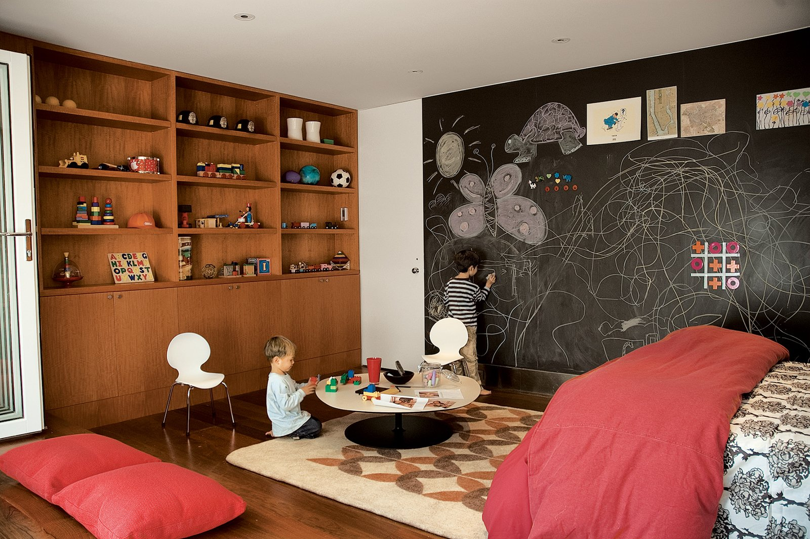 Garage, Garage Conversion Room Type, Living Room Room Type, and Attached Garage Room Type Writing on the walls is encouraged by the magnetic slate chalkboard from Claridge Products. The Phoenix table by Patricia Urquiola for Moroso does double duty as a play table or a coffee table, depending upon who's in residence. The Tulips felt rug is from Peace Industry, and was made in a fair-trade workshop in Iran. The casework is constructed of anigre wood.  Photo 4 of 4 in A Garage Converted Modern Playroom