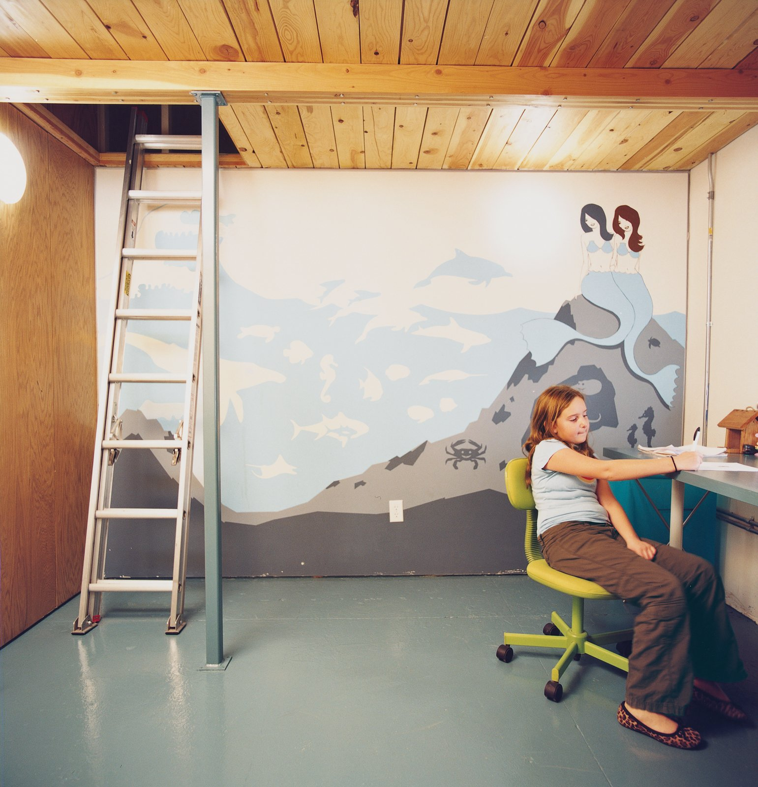 Eve works at the desk in her double-height bedroom. Vogt's mythically aquatic-themed mural reflects both the taste of a young girl and the pared-back aesthetic of any modern enthusiast.  Photo 9 of 10 in A Minneapolis Building That Has Lived Multiple Lives Is Revitalized by a Coffeehouse Owner