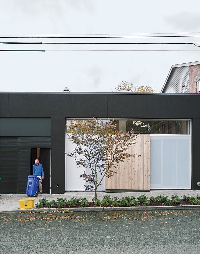Exterior, Wood Siding Material, Glass Siding Material, Flat RoofLine, Concrete Siding Material, and House Building Type Perforated metal screens, one of which doubles as the front door, shield the storefront window from the street.  Photo 10 of 12 in This Light-Filled Industrial Renovation Plays Host to Live Music