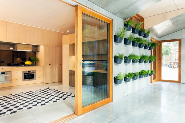 "There are two zones in the house. One side, which the architects refer to as the ""buffer zone,"" faces north, capturing the sunlight in the winter and pulling it into the house. In the summer, it traps the harsh sun so less gets into the living space. Edible planters adorn the wall."