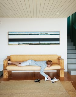 Will relaxes on the sofa Gerald designed, below a painting by Gary Freemantle.