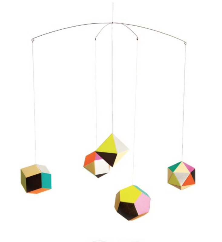 Spot color printed balls of woodfree paper dangle kaleidoscopically above children with the Themis Mobile. The mobile's geometric patterns designed by Clara von Zweigbergk modernize this classic.