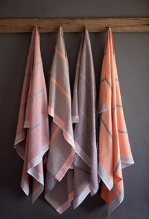 Itawuli by MungoMungo's flat-weave towels, made on antique looms in Plettenberg Bay, have traditionally reflected a strong British influence. But they've taken a detour with their new diamond weave towels in colorways like mulberry with partridge brown, hot orange, and forest green. While the pattern has an echo of traditional shweshwe fabric from the Eastern Cape, the contrasting stripe is more typical of Basutu blankets. Made of 100% cotton from Swaziland.