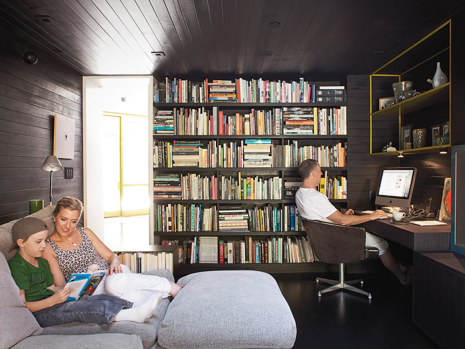 """Office, Study Room Type, Bookcase, Shelves, Desk, and Dark Hardwood Floor In the den, Lara and Cal read a Hardy Boys mystery on the Flexform Groundpiece sofa by Antonio Citterio while Chris works in his """"office."""" The cozy room where the family spends much of their time once housed the kitchen.  Photos from Designed In-House"""