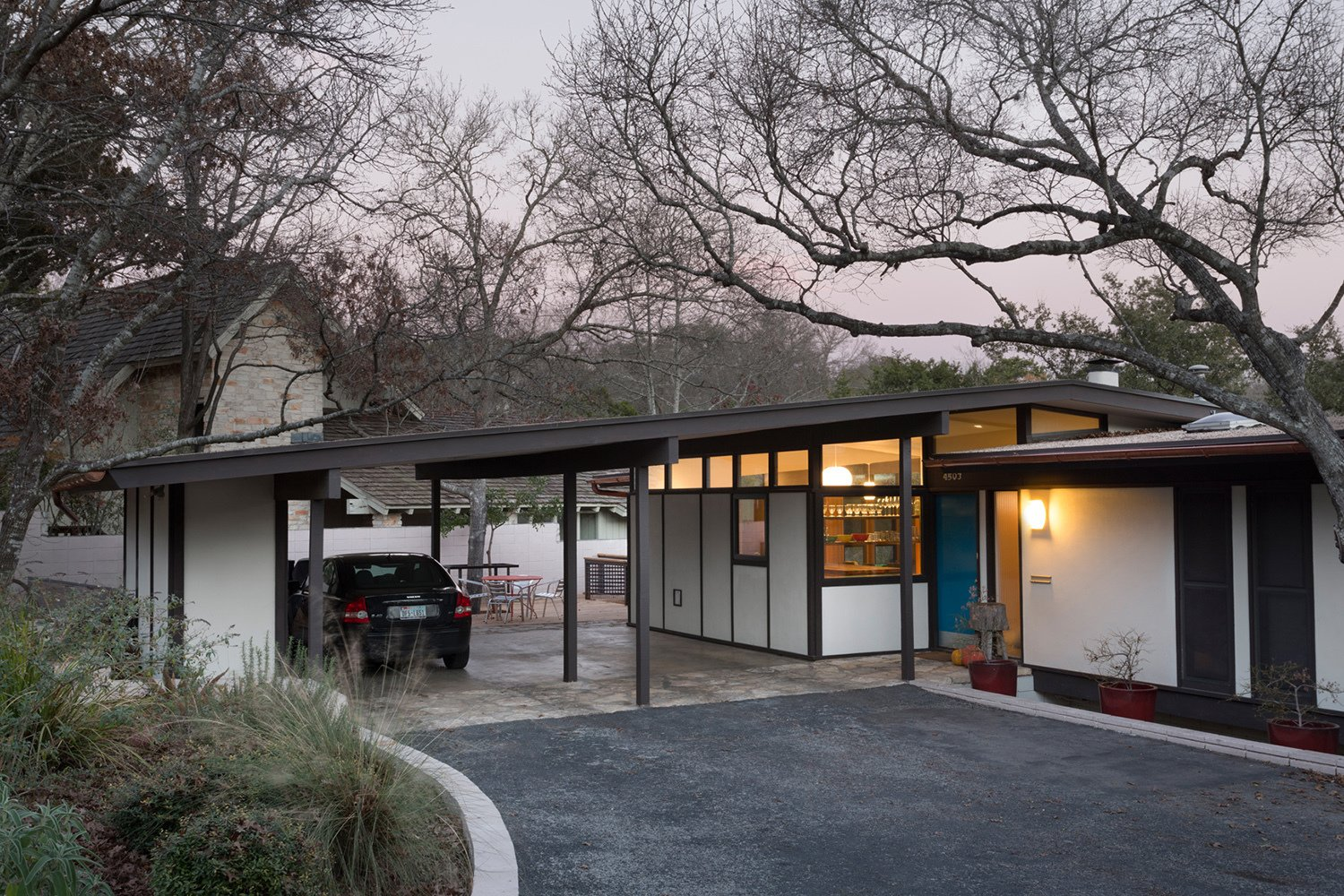 A wide view of the renovated home situates it as it sits on Austin soil. Where the gentle swoop of the driveway meets the overhanging garage, the home's patio is just visible. A light in the new kitchen window further integrates the home with the neighborhood just beyond it.  Photo 1 of 13 in Midcentury Renovation in Austin