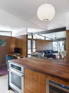 A post-renovation view of the kitchen shows it opening into the family room. Replacing the former white cabinets are Island drawer fronts and wall panelling of teak wood and reclaimed American elm countertop, milled by Vintage Material Supply. The differing grains of the teak veneers and elm countertop vadd complexity and rhythm to the kitchen's wood motif. Stuc Pierre plaster ceiling selected by the homeowner, Sloan Houser, adds an airy feel to the opened space.