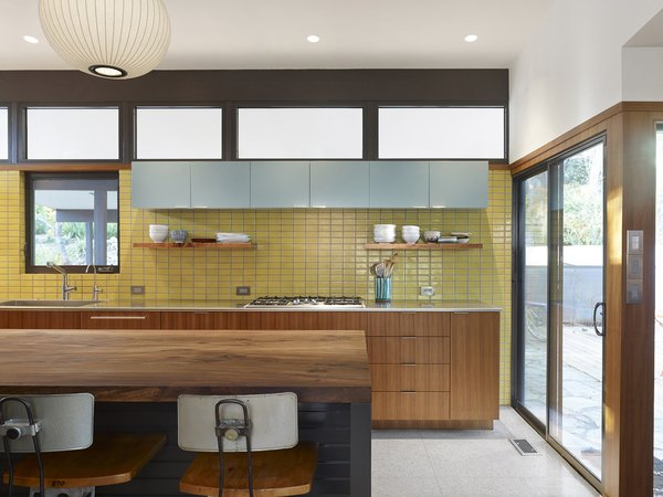 A view of the kitchen's back wall shows the bright marriage of the yellow Fireclay tile backsplash with incoming light from the adjacent sliding door and the row of windows just above the hanging Boca Raton blue cabinets. Basked in light, the new kitchen displays an organized and cheerful aesthetic.
