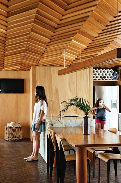 "O'Sullivan designed the ceiling ""to have a knitted or woven quality like that of wool or silk."" It dives down over the kitchen and dining area, eventually reaching a point at the entry that is low enough to touch. Here, resident Jes Wood leans against the onyx kitchen island while her daughter Ruby hangs out. Replica Jean Prouvé chairs surround the dining table; a vase by Bruce and Estelle Martin for Kamaka Pottery sits on top. The Reel table under the television is by Atelier Oï for B&B Italia."