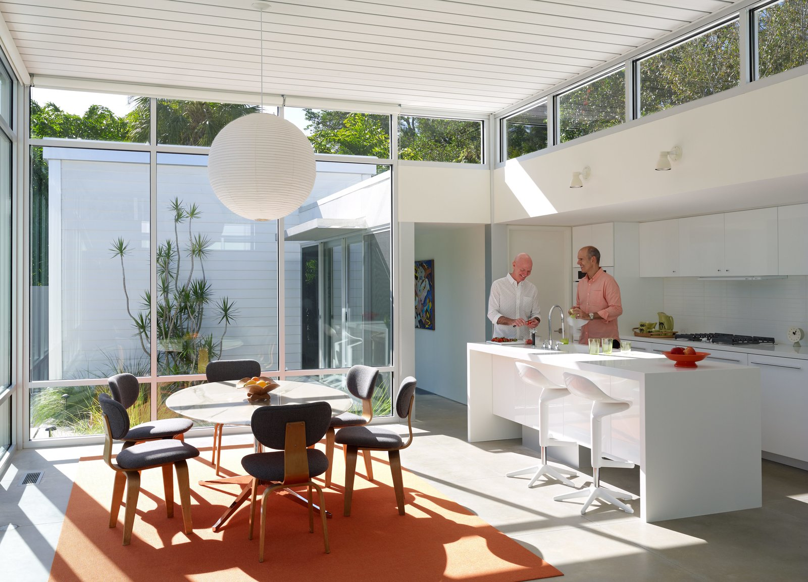 Kitchen, White, Wall, Pendant, Concrete, and Cooktops In the kitchen, Pirman and Tetreault gather around a custom Corian island with a Tara faucet by Dornbracht. Vintage Cees Braakman Combex series chairs and a marble Florence Knoll table bring natural materials to an architectural shell built from concrete, glass, and steel.  Best Kitchen Concrete White Cooktops Photos from This Sparkling New Home Is a Perfect Remake of Classic Sarasota School Modernism
