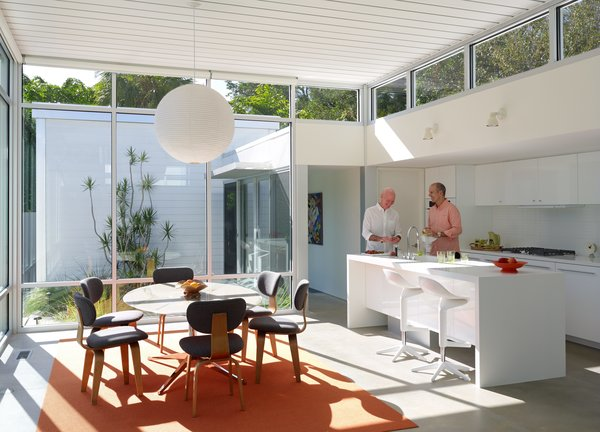 In the kitchen, Pirman and Tetreault gather around a custom Corian island with a Tara faucet by Dornbracht. Vintage Cees Braakman Combex series chairs and a marble Florence Knoll table bring natural materials to an architectural shell built from concrete, glass, and steel.
