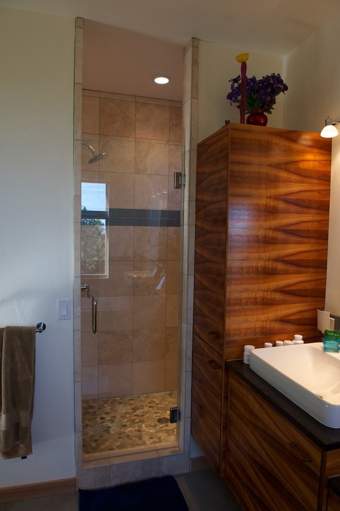 The custom koa-veneer cabinetry also found a home in the master bathroom. Photo by Barry B. Doyle.  Photo 5 of 8 in Mountaintop Modern