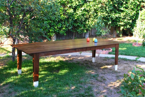 A nine-foot solid walnut dining table (shown) was made for a couple that fell in love with Grace's desk. The table was designed specifically to their preferences and plate sizes. Sevak painted the legs white to visually separate the table from the hardwood floors in the house.