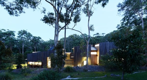 """The house's location on a fire-prone site on the edge of a wooded area posed a challenge for Blue. He used a mix of steel and fire-resistant timber to construct the residence. Another challenge was to """"crop out"""" the neighboring houses so Blue oriented the structure so that it opens to its own garden and views of the forest."""