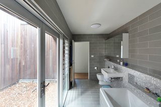 The bathroom features floor-to-ceiling glass walls and louvered windows to help the narrow space feel larger.