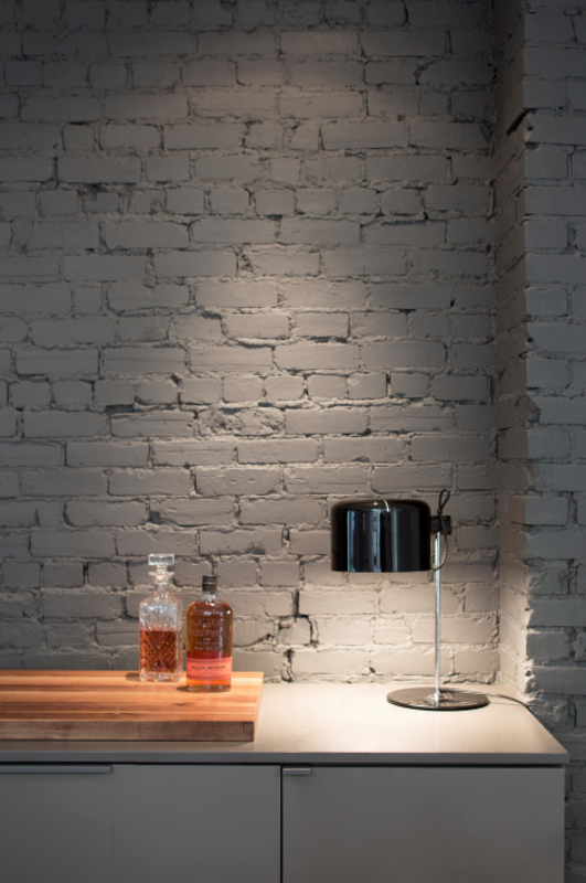 "The kitchen's exposed brick wall matches its cabinetry in Benjamin Moore's ""Kendall Charcoal"" hue. A Joe Colombo Coupé 2202 table lamp by Oluce illuminates a walnut cutting board."