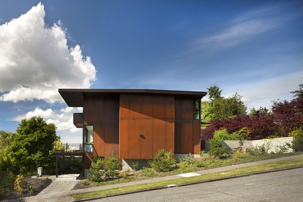 Exterior, Metal Siding Material, and House Building Type The Hammer House in Seattle is clad in weathered steel panels, which provide privacy from the busy street. Natural light enters from a glass-walled bay directly behind the opaque wall. Photo by: Nic Lehoux  5 Ways to Use Steel in Modern Homes by Allie Weiss from Olson Kundig Houses