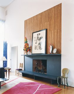 In a converted church in Connecticut, a modern fireplace and mantel design incorporates a ledge that functions as a bench and place for holding artwork or extra firewood. Above the fireplace, a Warhol collage is surrounded by a papier-mâché sculpture of no special provenance, a Vigliaturo glass piece, and a Picasso plate.