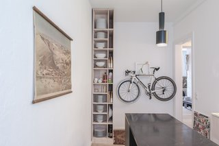 Kitchen of the Freunde von Freunden X Vitra Apartment  Architect Etienne Descloux adjusted the original bathroom design to provide more space for storage in the kitchen. Bike by Mikili, flowers by Marsano.  Photo by Steve Herud