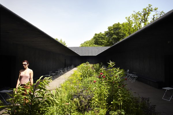 2011: Peter Zumthor  Wrapped in stark, black wood, Swiss architect Peter Zumthor's Serpentine scheme presented a frame for Piet Oudolf's lush garden, a use of color and space that manages to create a secret garden in an already outdoor space.  Photograph © 2011 Walter Herfst