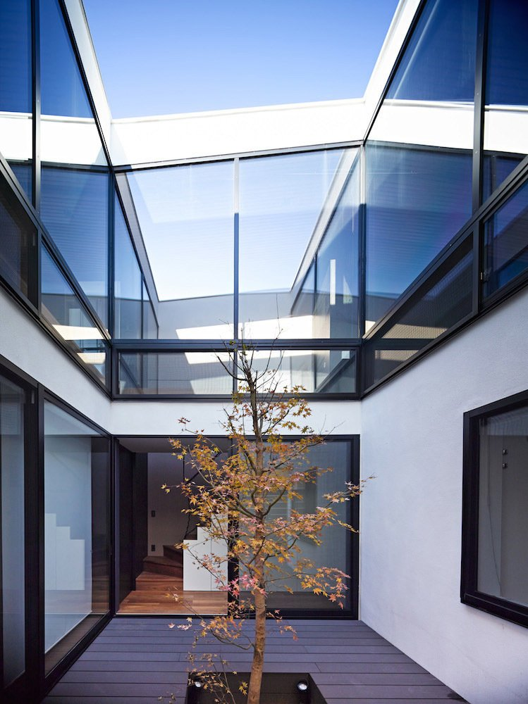 The home's forms, which are masked by the cantilevered entrance, become apparent once one enters the central courtyard. Living spaces abut three of its sides, looking in with full-height windows. The roofline can be seen fluctuating as one goes from front-to-back. The memorial tree, around which the courtyard and home are built, will continue to grow in coming years.  Photo 3 of 11 in These Courtyards Bring Indoor/Outdoor Living to 10 Modern Homes from These Modern Surf-Side Homes Are Just Swell