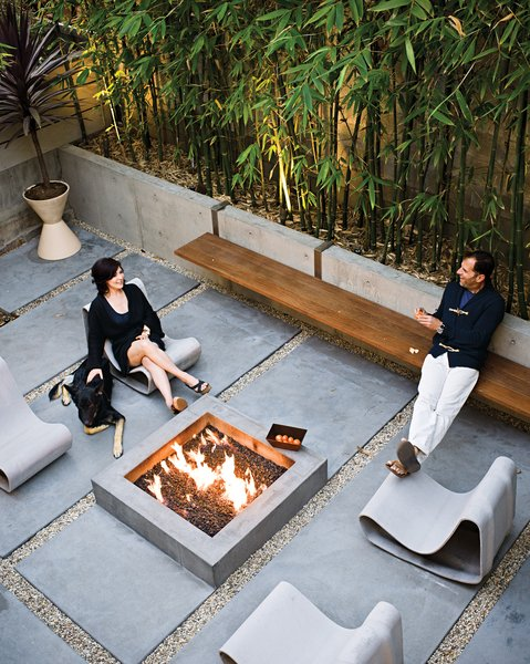 In a Manhattan Beach home, homeowner Matt Jacobson and architect Michael Lee designed the long steel-and-Ipe bench surrounding a square, concrete outdoor fire pit, which suspends from the low concrete wall in their outdoor space. Dukes relaxes on a Willy Guhl Loop chair with her German Shepherd, Major.