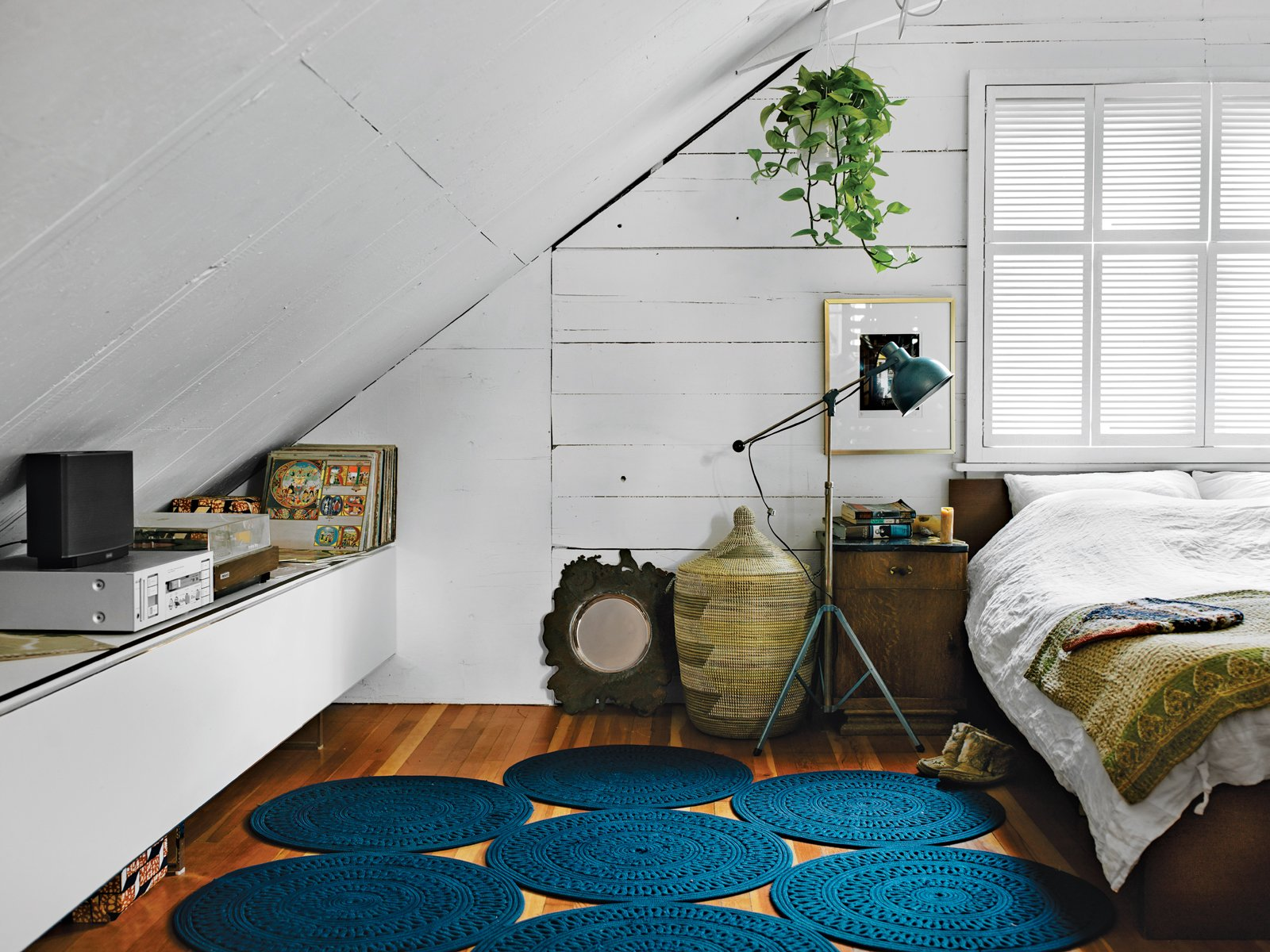 In the bedroom, a light by Bretford in Chicago is next to an Ikea Malm bed topped with Indian linens and folk weavings. The rug is from Paola Lenti. A Bocci 19 brass bowl sits near a hamper from Connected Fair Trade Goods.  How to Frame Space With a Graphic Rug by Aileen Kwun from Modern Interiors in British Columbia