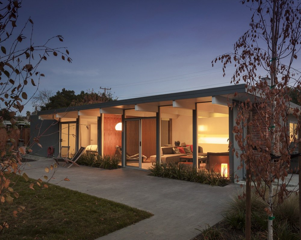 Exterior, Mid-Century Building Type, and House Building Type A wall of windows provides a smooth transition between indoor and outdoor spaces in this renovated home. Open to the fenced-in yard, the patio is as intimate as the living room and bedroom just inside. Photo by: Scott Hargis  Modern Eichler Renovations by Allie Weiss from A Renovated Eichler Home in San Rafael, California