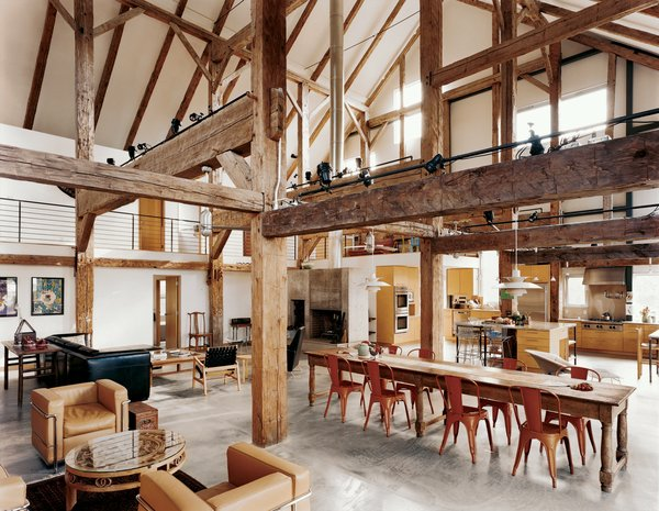 """""""We didn't want to diminish the openness and height and feeling of a great expanse of space,"""" said the owner of this resurrected 19th-century barn house in Pine Plains, New York. Fortunately, the barn frame's horizontal beams perform a domestic function by creating the illusion of a lower ceiling. An abundance of furnishings in rich materials fills out the space. Photo by Raimund Koch."""