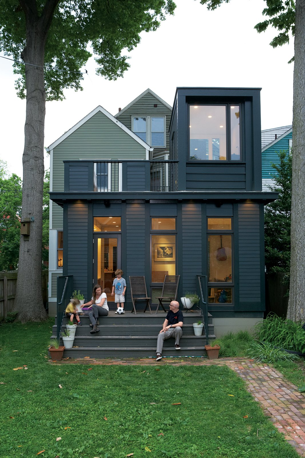 Juliet Gray, Mathias Kolehmainen, and their sons Cooper and Cyrus have a new favorite hangout: the wide back steps on the addition, which double as theater seating. (They project movies from the second-floor balcony onto an out-building across the yard.)  Photo 4 of 5 in Modern Addition in Louisville