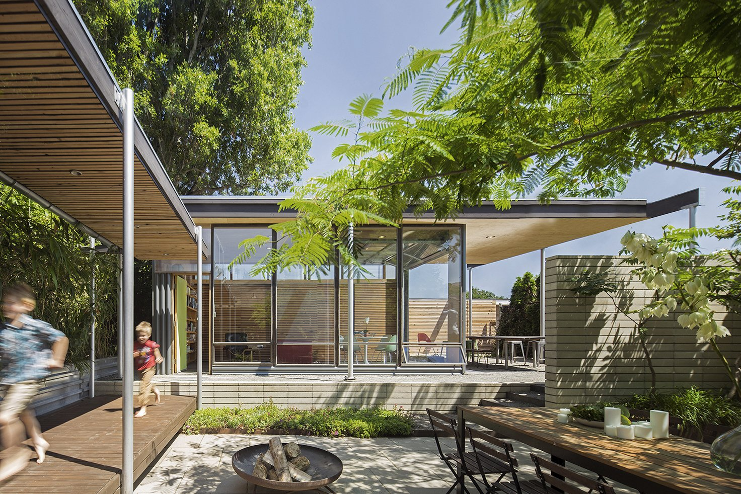 Exterior A covered walkway provides a sheltered passage between the main house and studio. The fire pit is used during social gatherings.  Best Photos from A Blissful Retreat Replaces a Scrap-Filled Yard in Seattle