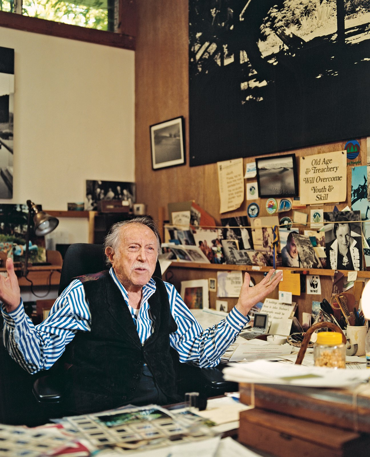 """""""A wonderful mess"""" is how Shulman describes his desk. Interspersed among the family snapshots, mementos, and tchotchkes are several enlarged quotations, including one from Art News: """"If buildings were people, those in Julius Shulman's photographs would be Grace Kelly: classically elegant, intriguingly remote.""""  Photo 1 of 4 in True Hollywood Story"""