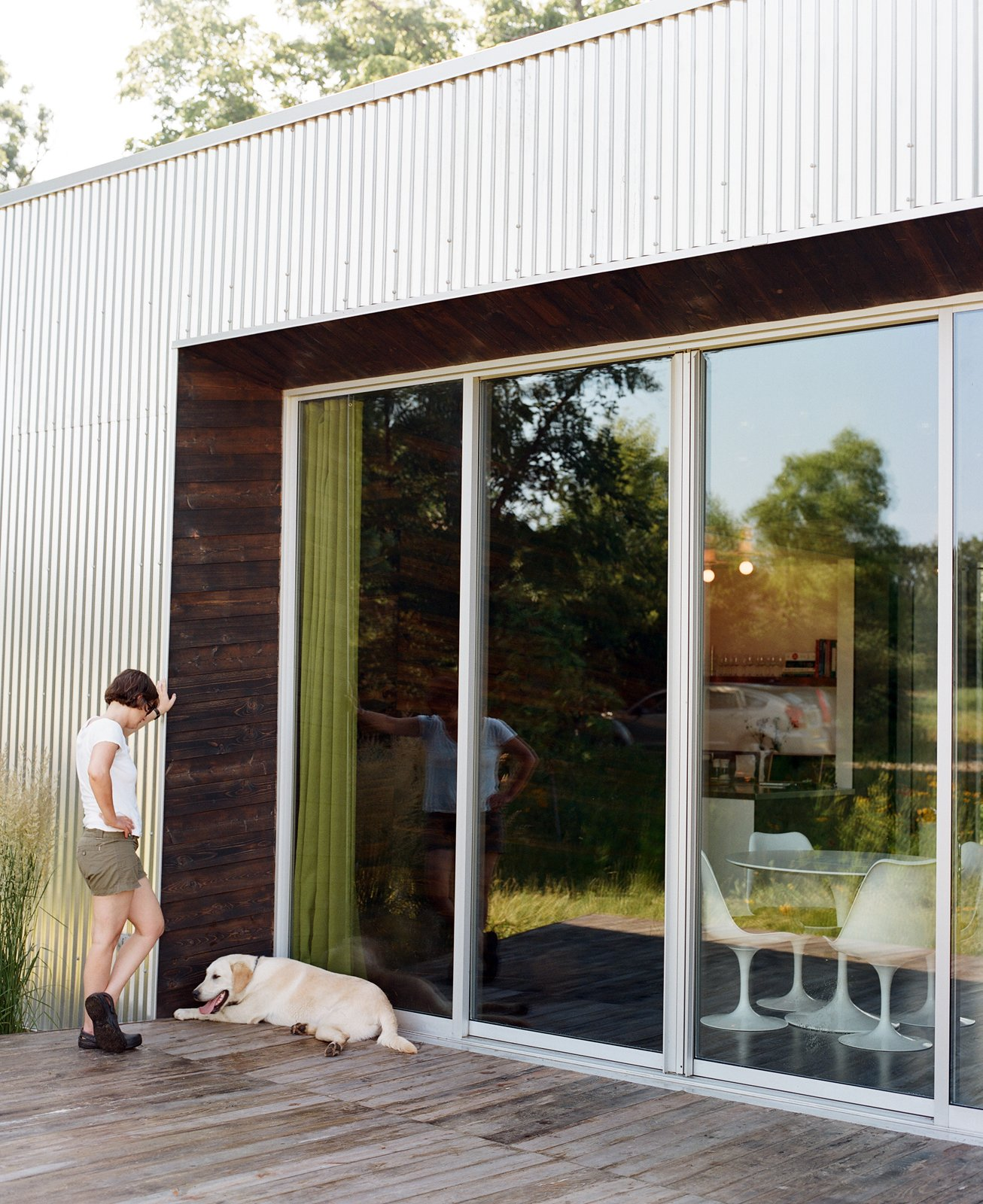 Outdoor and Wood Patio, Porch, Deck Out on the deck, Pascal enjoys some relaxed time with their dog, taking a breather in a bit of shade while sun streams across the meadow.  Photo 11 of 25 in Leap Into the Year of the Dog With These 25 Pups in the Modern World from How To: Inviting Front Doors for Modern Homes