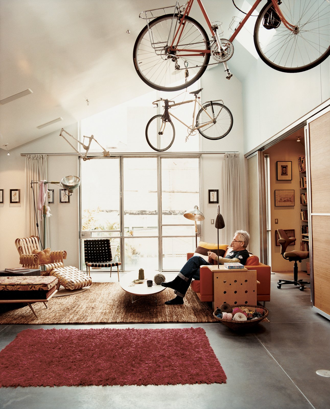 The living room is a comfortable melange of pieces Baker grew up with, such as the Robsjohn-Gibbings chaise, and ones he's added, such as the Frank Gehry Power Play club chair.  Frank Gehry Designs in Modern Homes by Zachary Edelson from Mission Statement
