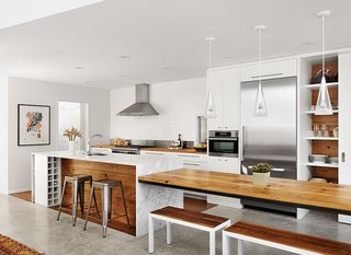 Architect Kevin Alter integrated wood from the original bungalow into the kitchen and covered the island in Carrara marble, with an interior clad in wood. A long table extends from the side of the island, and wine storage is integrated into one end of the island. New appliances include a Wolf range, a Broan hood, and a Miele oven and refrigerator. The Fucsia pendant lights are by Achille Castiglioni for Flos.