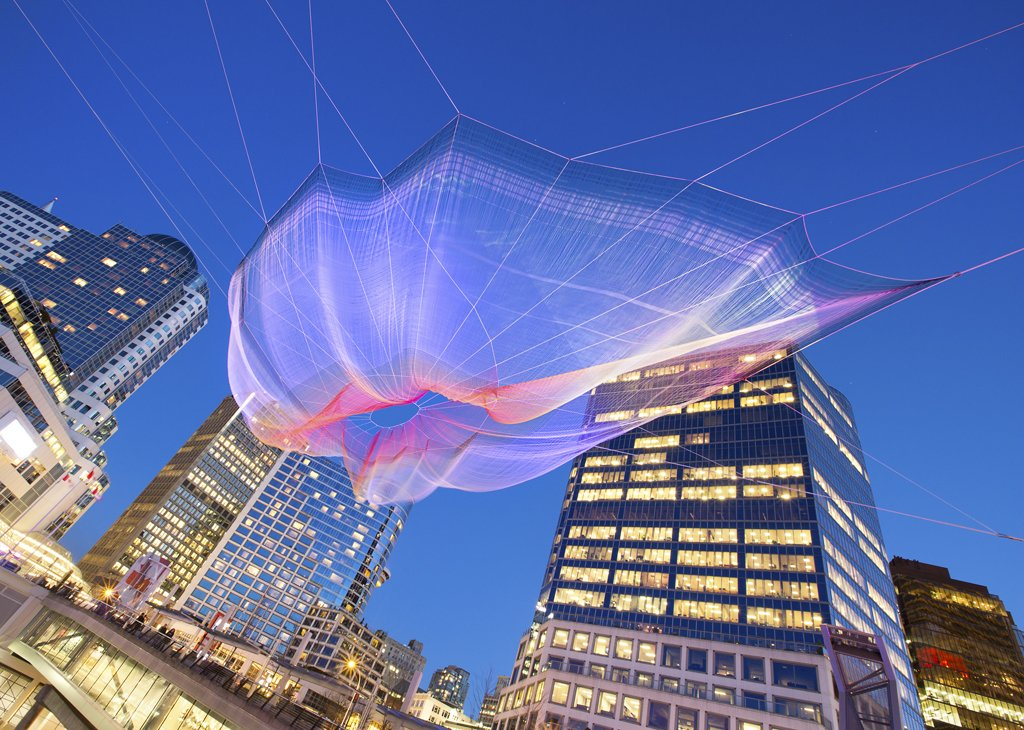 "Janet Echelman's ""Skies Painted with Unnumbered Sparks""  Created to celebrate the 30th anniversary of the TED Conference and only up from March 15-22, the web of netting suspended between the Fairmont Waterfront and the Vancouver Convention Center was a wonder. Echelman says her work is, in part inspired by the idea of ""feeling sheltered, but connected to the limitless sky,"" and the crowds that gathered and interacted seemed to feel similarly inspired.  Credit: Ema Peter  Photo 1 of 4 in Sculpture Lets the Public Paint the Sky"