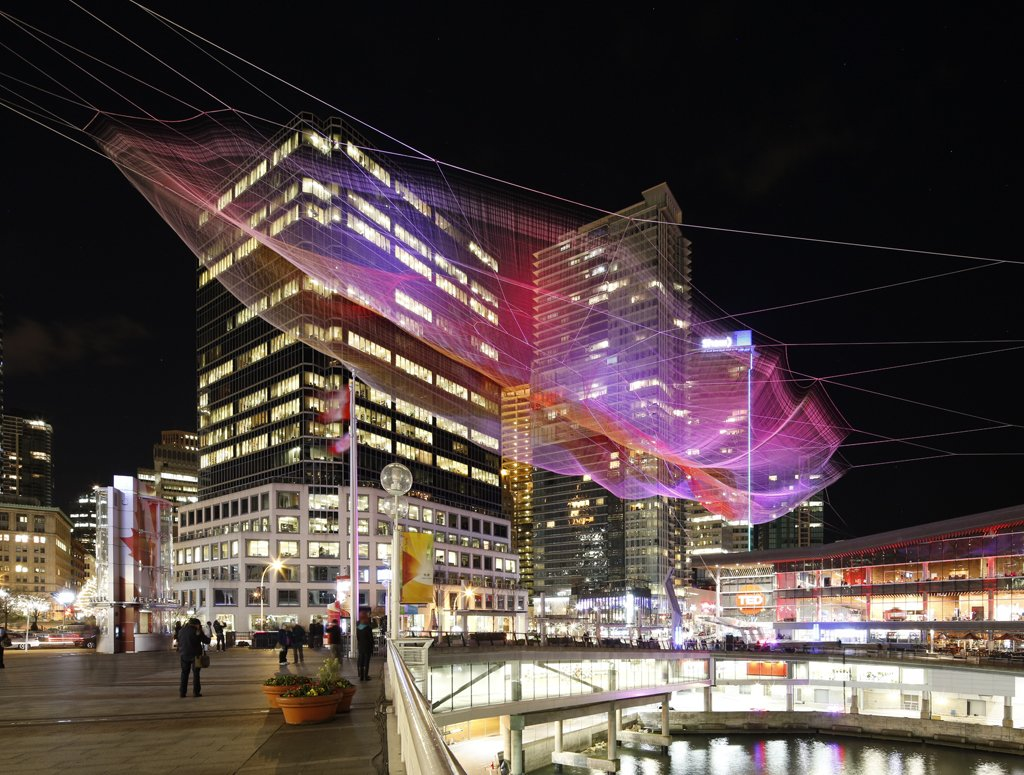 "Janet Echelman's ""Skies Painted with Unnumbered Sparks""  The sculpture combined Wolverine-like strength, sophisticated technology and gorgeous execution, and was a massive technical challenge for Echelman and the team of more than 100 designers and engineers. Aaron Koblin, Creative Director of the Data Arts Team in Google's Creative Lab, designed the public interface, which literally allows pedestrians to walk by and ""paint the sky"" with an open mobile browser.  Credit: Ema Peter  Photo 3 of 4 in Sculpture Lets the Public Paint the Sky"