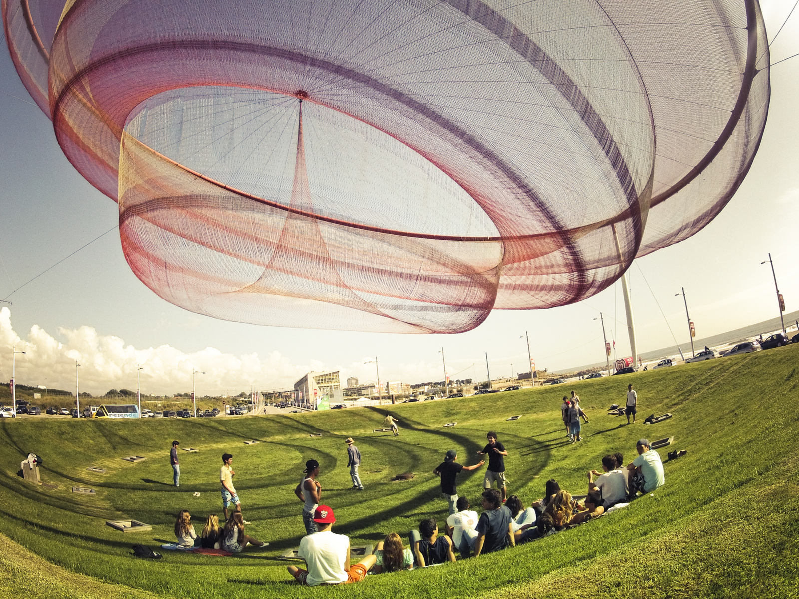 """Janet Echelman's """"She Changes""""  One of Echleman's previous pieces, located in Porto, Portugal, it has inspired people to gather underneath, even though it's located across from a four-lane highway.  Credit: Enrique Diaz  Photo 4 of 4 in Sculpture Lets the Public Paint the Sky"""
