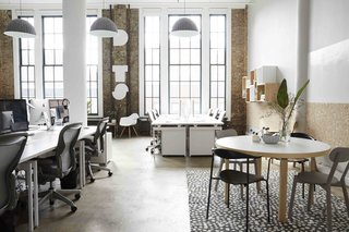 """The new office makes the most of the exposed brick, tall ceilings, and large southfacing windows. """"Because we are based in New York, we don't have a ton of space,"""" says Dots co-founder Patrick Moberg. """"We wanted a clean, thoughtfully designed place to build and play games."""" Murphy interpreted these wishes into an aesthetic she describes as """"traditional American office meets Scandinavian home."""""""