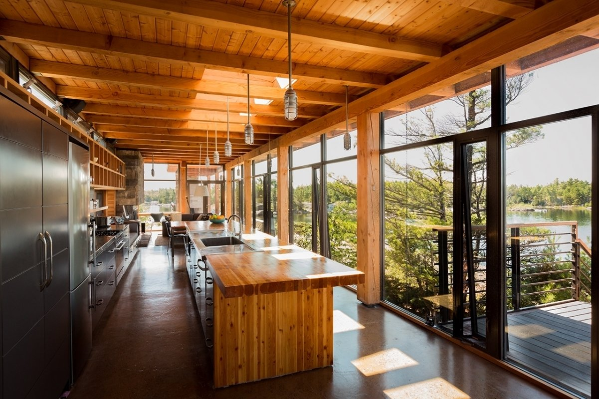 The home maintains remarkable material consistency, with Douglas fir cladding the beams, kitchen countertop, and interior walls. The open-plan kitchen absorbs views of the lake through an expansive glass wall.  Kitchens with Killer Views by Andrea Smith