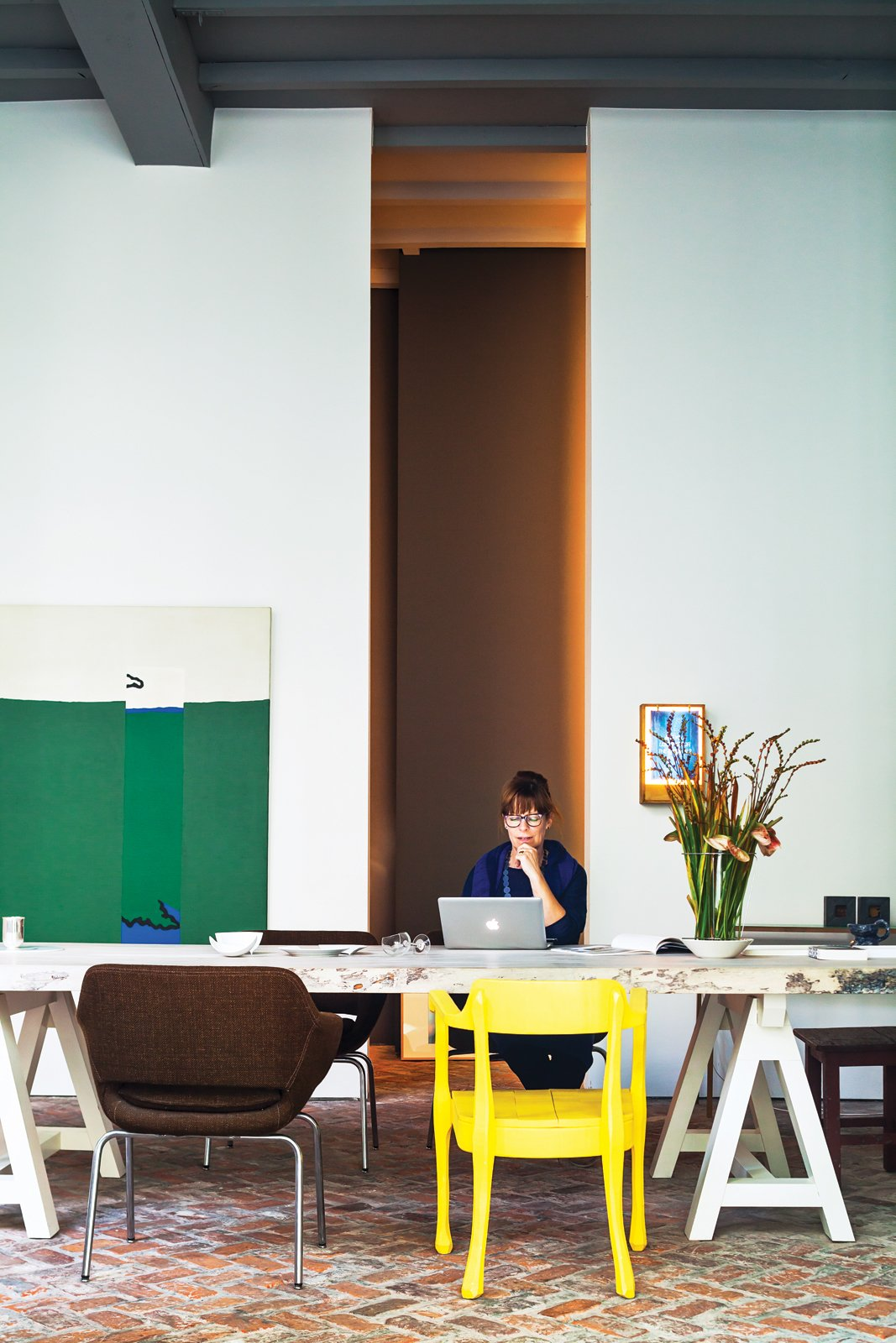 Office, Desk, and Chair With the help of architect Bart Lens, Veerle Wenes and Bob Christiaens merged a 19th-century building with a 1970s one to create a combined home and art gallery in Antwerp. In the dining room downstairs, Wenes entertains family, friends, and gallery visitors. The yellow chair is by Jens Fager.  Best Photos from This House Proves Art Galleries Can Be Super-Friendly