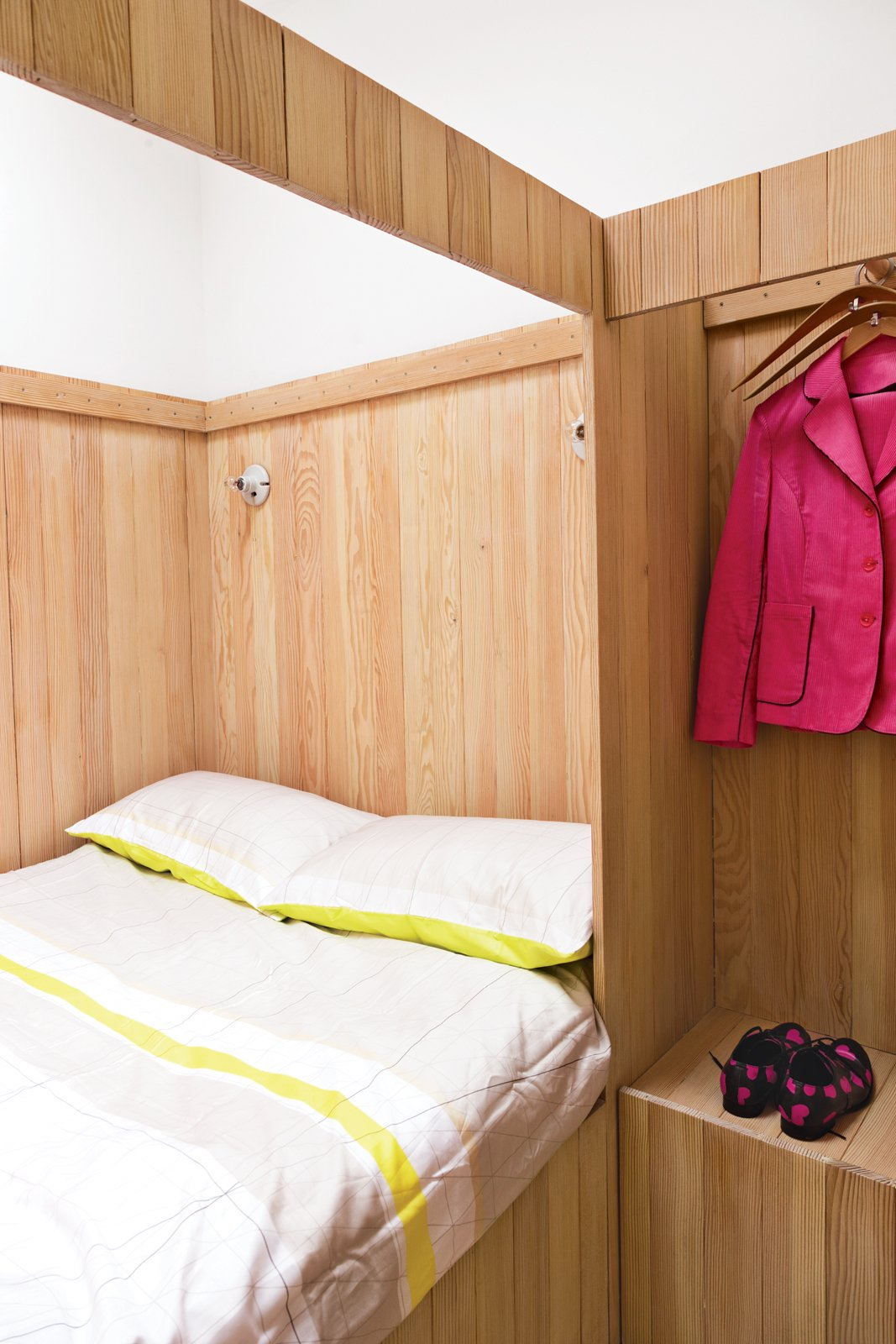 Bedroom, Bed, and Storage A closet is built into the bed frame in this London guesthouse. With hangers so close by, there's no excuse for not hanging up your clothes before bed. Photo by Ben Anders.  Photo 5 of 10 in A Colorful, Custom-Built Guesthouse in London