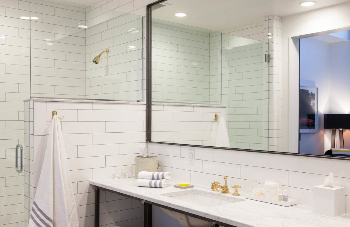 The bathrooms are stocked with Malin + Goetz toiletries and towels from the Nashville linen maker Turkish-T. The walk-in showers are lined with white subway tile. Photo by Caroline Allison.  Photo 6 of 6 in The 404: Nashville's Newest, Smallest, Hotel