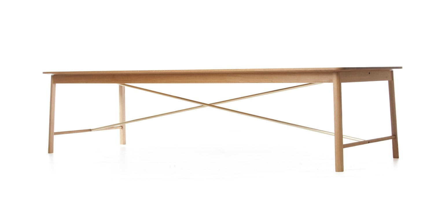 "Flatiron Dining Table with Solid Brass Stretchers by Soren Rose for De La Espada  ""The Flatiron was done for apartments in the building of the same name in New York. It's a simple table. Brass happens to be a hot material right now, and it's used in a necessary and a sparing way. It's not just an adornment, it's not spoiling the integrity of the table. Having that flourish underneath the table, it takes a moment to recognize it. I like that type of design, where what makes it special isn't the first thing that you see.""  Photo 3 of 11 in Shops We Love: Propeller Modern"