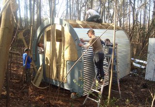 Volunteers for Mad Housers Inc. build an enclosure out of wood and corrugated metal. The Atlanta-based nonprofit build modest structures for homeless people with a goal of giving them a sense of security, privacy, and dignity. Photo courtesy of Mad Housers Inc.