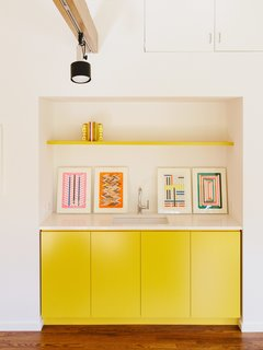 In the office, existing track lighting illuminates cabinetry covered in Lemon Bar by Miller Paint.