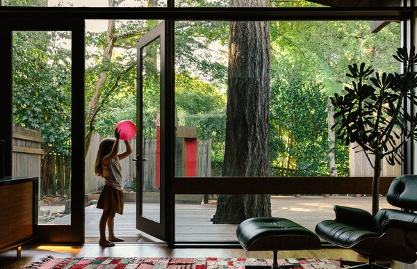 With four children under the age of six, the Ruells have learned not to be overprotective of their collection of contemporary and vintage furniture. In the living room, an Eames lounge chair and ottoman sit on a Moroccan rug from M.Montague, while the family's eldest child, Mirene, surveys the indoor/outdoor view. Throughout the house, Kolbe windows and fixed glass (in existing jambs) were added to increase energy efficiency.